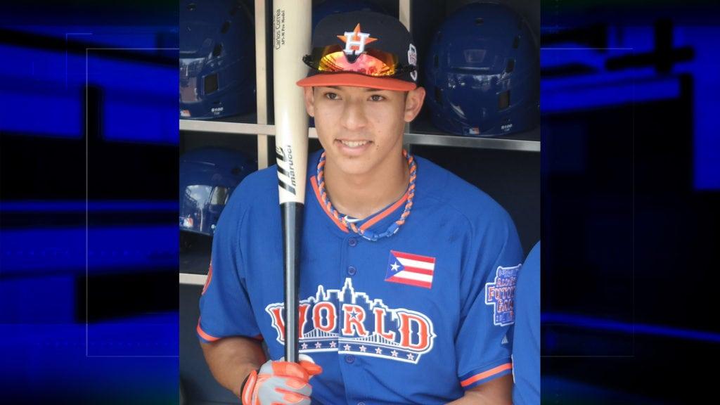 Carlos Correa holding bat in dugout