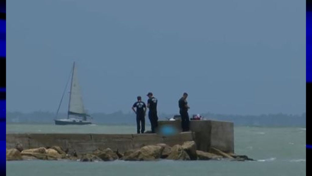 Crews work scene where a body was found floating in the bay.